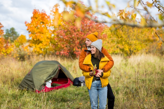 Concetto di viaggio, amore e autunno - giovane coppia innamorata in posa vicino alla tenda verde nella foresta autunnale
