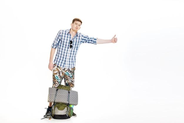 Uomo di viaggio che fa l'autostop giovane autostoppista maschio su sfondo bianco