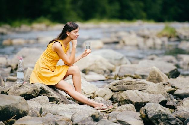 Viaggia in montagna. fiume con pietre sulla riva. tentazione di calore. la sete soffre. acqua potabile della ragazza soddisfazione del desiderio. occhi chiusi in pace e armonia. riposa nel piacere. stanco sotto il sole