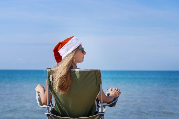 Viaggia la vigilia di capodanno sulla spiaggia dal mare ragazza con cappello di natale sta prendendo il sole in donna sole