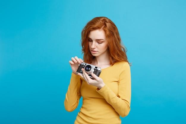 Ritratto di colpo in testa di concetto di persone e di viaggio della ragazza felice dei capelli rossi dello zenzero pronta a viaggiare con la macchina fotografica dell'annata nello spazio della copia della parete blu pastello di espressione felice