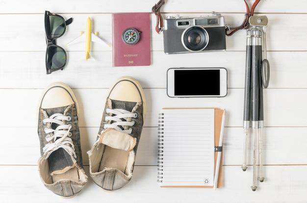 Piano di viaggio, vacanza viaggio, mockup di turismo - vestito del viaggiatore su fondo di legno bianco. distesi