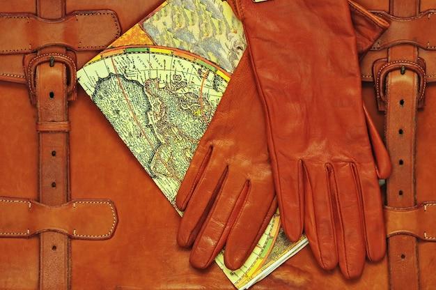 Mappa di pianificazione del viaggio valigetta in pelle e guanti su sfondo di legno