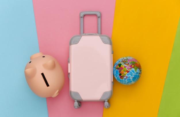 Pianificazione del viaggio. mini bagaglio da viaggio giocattolo, salvadanaio e mappamondo