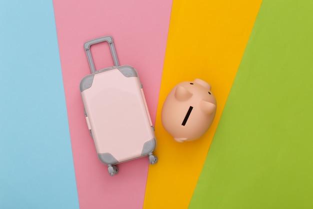 Pianificazione del viaggio. mini bagaglio da viaggio giocattolo e salvadanaio