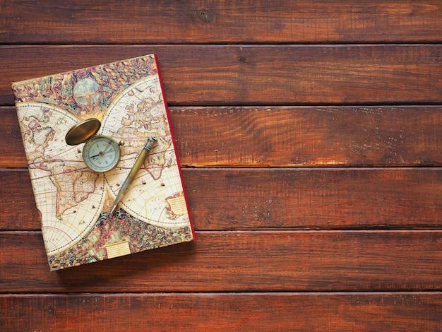 Pianificazione del viaggio vecchia mappa e penna della bussola su fondo di legno
