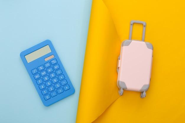 Pianificazione del viaggio. bagaglio da viaggio giocattolo e calcolatrice su carta blu gialla. lay piatto