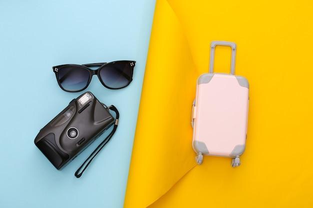 Pianificazione del viaggio. bagaglio da viaggio giocattolo, occhiali da sole e macchina fotografica su carta blu gialla. lay piatto