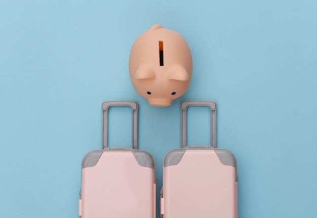 Pianificazione del viaggio. due bagagli da viaggio giocattolo e salvadanaio su pastello blu