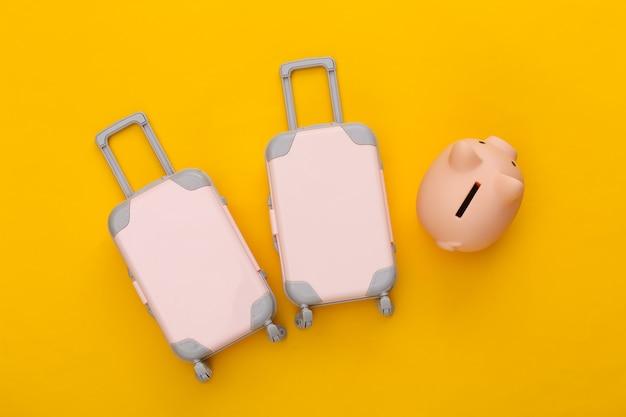 Pianificazione del viaggio. due bagagli da viaggio giocattolo e salvadanaio su giallo. lay piatto