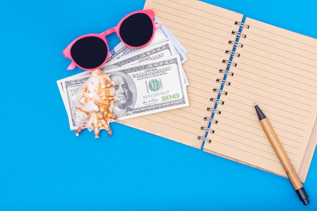 Pianificazione del viaggio, concetto di vacanza. su un taccuino vuoto aperto giacciono dollari, occhiali da sole rosa, una penna, una conchiglia su sfondo blu, vista dall'alto, copia spazio. può essere utilizzato in background, layout