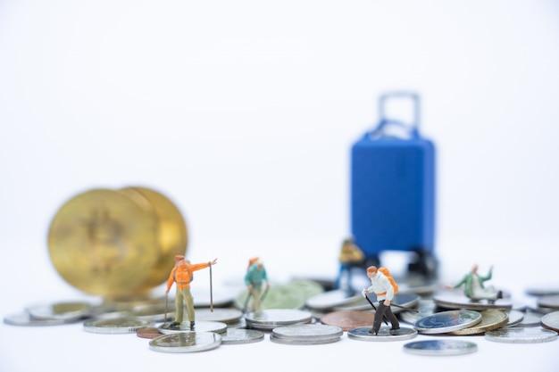 Viaggio e risparmio. persone in miniatura, viaggiatori con zaino che camminano su pile di monete e salvadanaio e bagagli come sfondo.