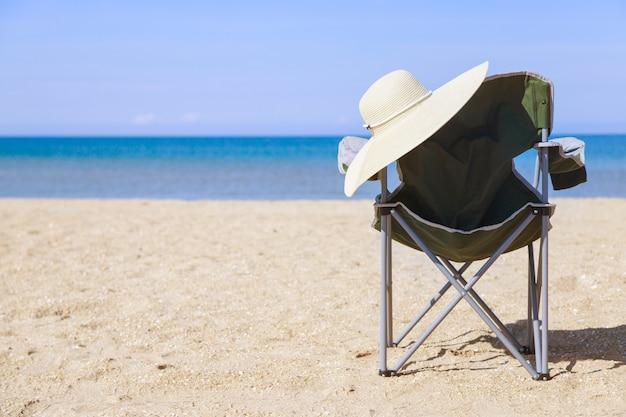 Viaggio al mare. sedia da campeggio e cappello sulla spiaggia