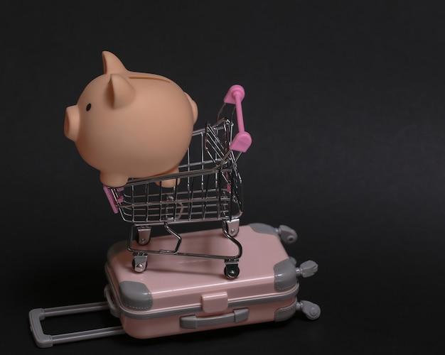 Concetto di viaggio e shopping. mini valigia da viaggio in plastica e carrello per supermercati con salvadanaio su sfondo nero.