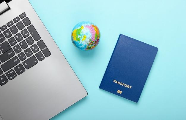 Viaggia ancora in vita. prenotazione online. emigrazione. laptop, globo e passaporto. accessori turistici su sfondo blu. vista dall'alto