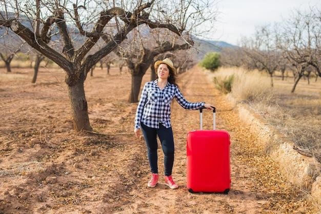 Concetto di viaggio, estate e persone. donna con valigia rossa in cappello