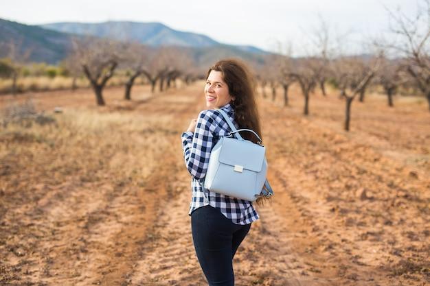 Concetto di viaggio, estate e persone. donna con zaino elegante sullo sfondo della natura. lei è in vacanza