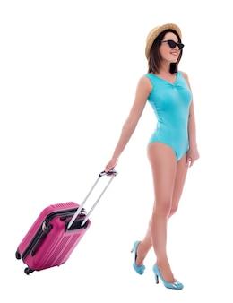 Concetto di viaggio e vacanza estiva - vista laterale della giovane bella donna in costume da bagno blu e cappello di paglia che cammina con la valigia isolata su sfondo bianco