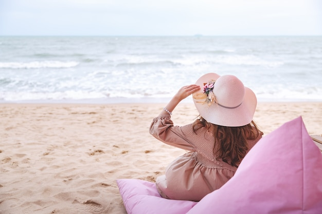 Il concetto di vacanza estiva di viaggio, la giovane donna asiatica felice del viaggiatore con il cappello ed il vestito si rilassa nel caffè sulla spiaggia di tutu, pattaya, tailandia