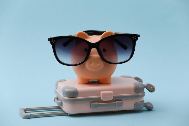 Viaggi, vacanze estive o concetto di turismo. mini valigia da viaggio con salvadanaio in occhiali da sole su blu