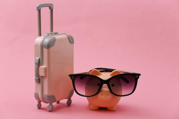 Viaggi, vacanze estive o concetto di turismo. mini valigia da viaggio con salvadanaio in occhiali da sole su rosa