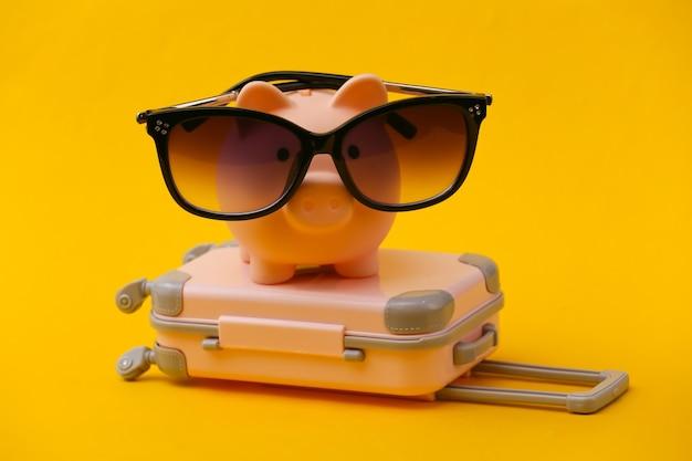 Viaggi, vacanze estive o concetto di turismo. mini valigia da viaggio con salvadanaio in occhiali da sole su giallo