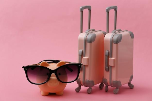 Viaggi, vacanze estive o concetto di turismo. due mini valigia da viaggio con salvadanaio in occhiali da sole su rosa