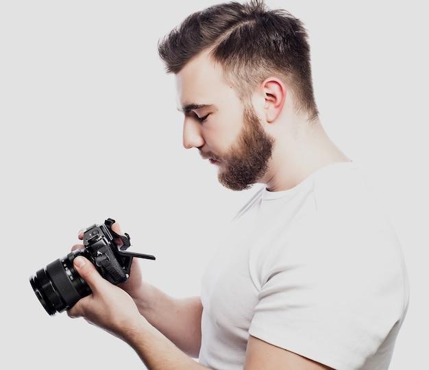 Concetto di viaggio, tecnologia e stile di vita: giovane fotografo barbuto che scatta foto con la fotocamera digitale.