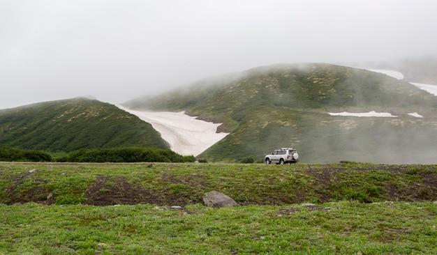 Viaggia in cima alla montagna, l'auto in montagna nella nebbia