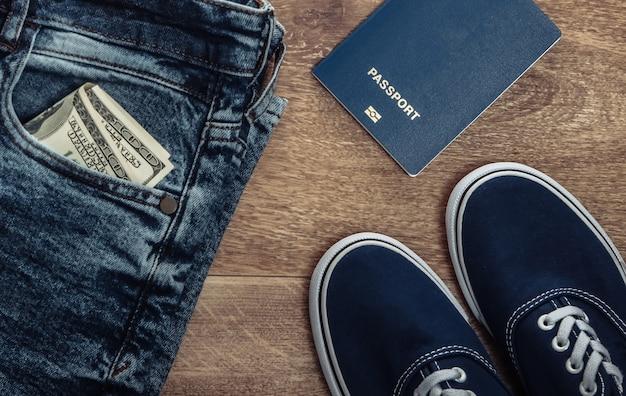 Concetto di viaggio o turismo. jeans, banconote da cento dollari, scarpe da ginnastica, passaporto su un pavimento di legno. vista dall'alto. lay piatto