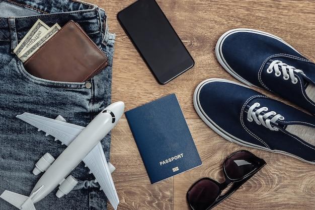 Concetto di viaggio o turismo. jeans, banconote da cento dollari, scarpe da ginnastica, smartphone, passaporto, occhiali da sole, aeroplano su un pavimento di legno. vista dall'alto. lay piatto
