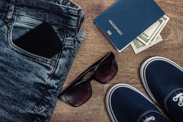Concetto di viaggio o turismo. jeans, banconote da cento dollari, scarpe da ginnastica, smartphone, passaporto su un pavimento di legno. vista dall'alto. lay piatto