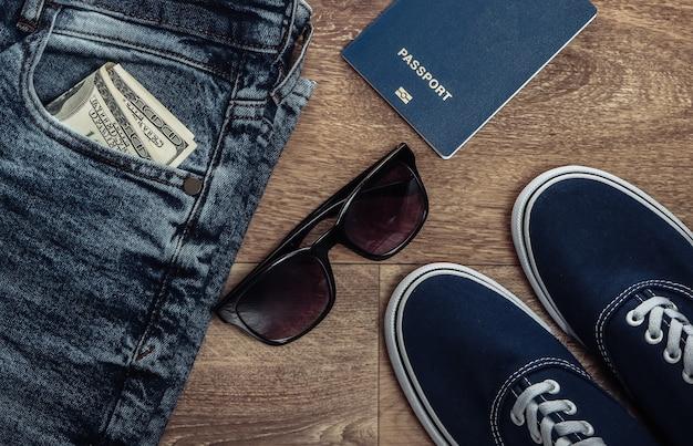 Concetto di viaggio o turismo. jeans, banconote da cento dollari, scarpe da ginnastica, occhiali da sole, passaporto su un pavimento di legno. vista dall'alto. lay piatto