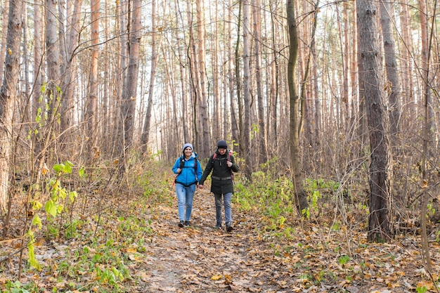 Concetto di viaggio, turismo, escursione e persone - coppia di turisti nella foresta di autunno.