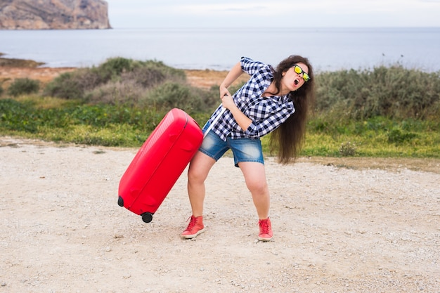 Concetto di viaggio, turismo e persone - giovane donna emotiva felice che viaggia in auto con due enormi valigie.