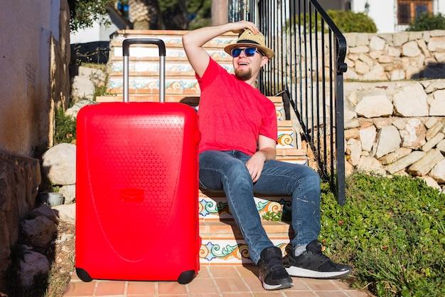 Concetto di viaggio, turismo e persone - uomo felice che si siede sulle scale in un cappello con la valigia rossa.