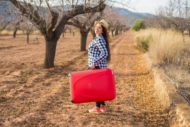 Concetto di viaggio, turismo e persone. giovane donna felice che viaggerà con la valigia rossa e sorriderà sulla natura