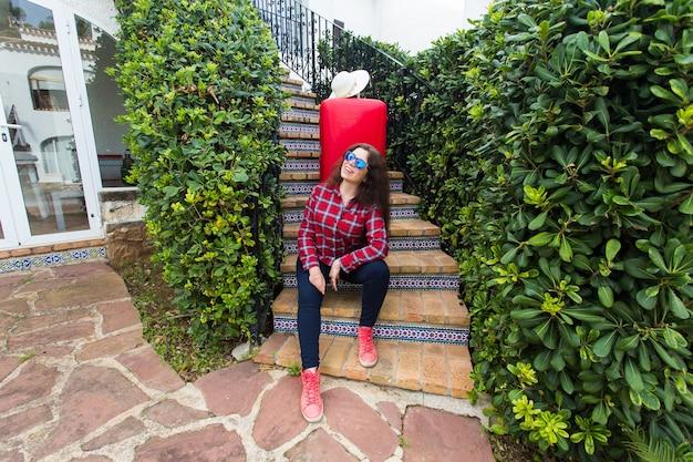Concetto di viaggio, turismo e persone - giovane donna felice che si siede sulle scale in vetri soleggiati con valigia rossa e cappello sdraiato su di esso.