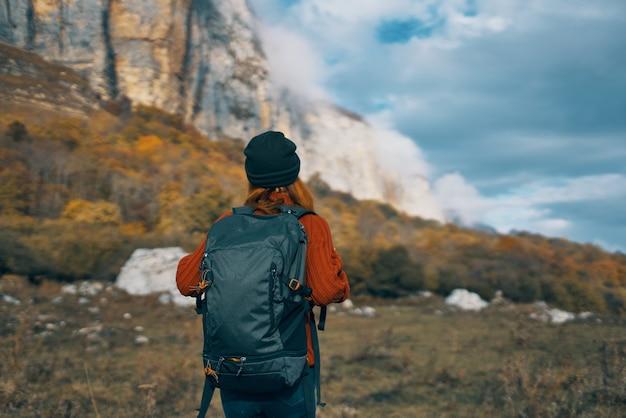Donna di turismo di viaggio con paesaggio del cielo di alte montagne dello zaino