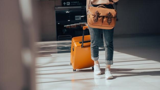 Turista di viaggio con bagagli o valigia in aeroporto Foto Premium