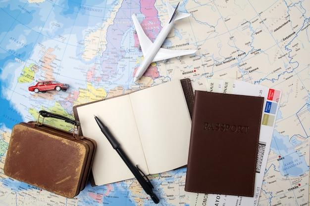 Viaggi, vacanze in viaggio, turismo - taccuino da vicino, valigia, aeroplano giocattolo sulla mappa.