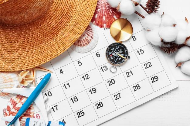 Concetto di viaggio e vacanza, bussola sul calendario planner