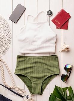 Concetto di viaggio e vacanza. oggetti da viaggio piatti laici con costume da bagno, smartphone, passaporti, occhiali da sole e bussola su fondo di legno bianco