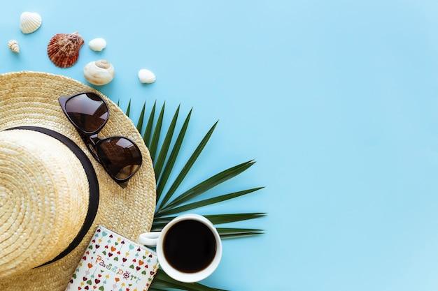 Viaggi, concetto di vacanza. cappello con conchiglie di mare, foglia di palma, passaporto, occhiali da vista e tazza di caffè su sfondo blu.
