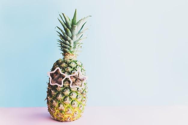 Concetto di viaggio e vacanza con ananas che indossa occhiali da sole. occhiali rosa a forma di stella. relax sul mare.