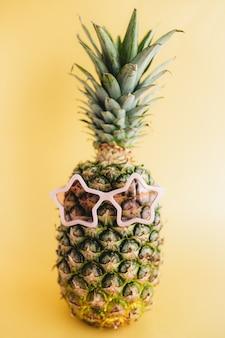 Concetto di viaggio e vacanza con ananas che indossa occhiali da sole. occhiali rosa a forma di stella