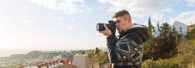 Fotografo per vacanze di viaggio e concetto di autostoppista viaggiatore uomo fotografato montagne e città