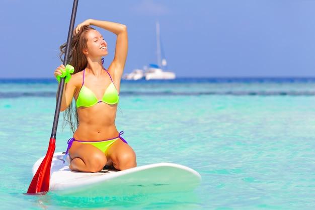 Carta da parati di vacanza di viaggio - la bella giovane ragazza bionda in bikini si rilassa nel mare
