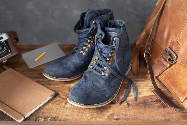 Viaggia vintage vecchie scarpe stivali al tavolo scrivania in legno vicino al muro di cemento texture di sfondo surface