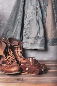 Viaggia vintage vecchie scarpe stivali al tavolo di legno e giacca, muro di cemento texture di sfondo surface